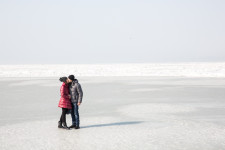 A young couple kissing on the ice-covered sea in Vladivostok.