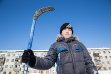 A young boy standing tall on the ice hockey rink.