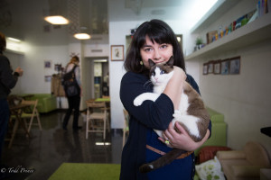 Alyona holding one of the cats inside her time cafe.