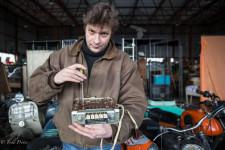 Mikhail fixing a radio for a GAZ 21 Volga car.