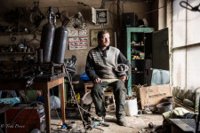 Dmitry in his garage holding one of his sculptures.