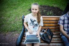 Anna sitting in the park learning to build a website.