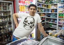 Nodir standing inside the convenience store he works at.