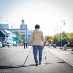 A retired woman walking along the refurbished seaside.