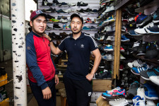 Azim (right) with a a friend at his shoe kiosk in a Bishkek market.