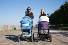 Friends and first-time mothers out for a walk with their newborn children.